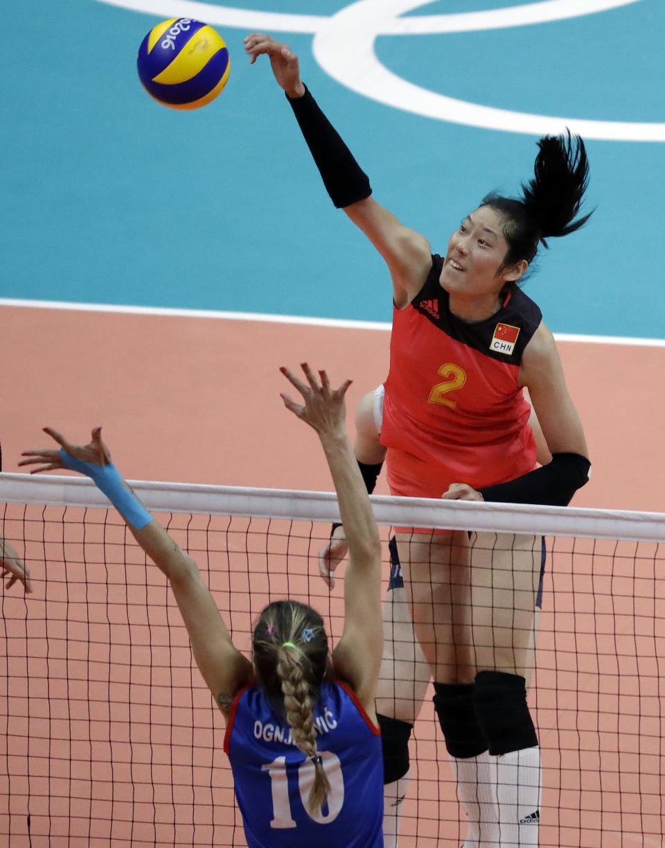 FILE - In this Aug. 12, 2016, file photo, China's Zhu Ting, top, spikes the ball over Serbia's Maja Ognjenovic during a women's preliminary volleyball match at the Summer Olympics in Rio de Janeiro. The Chinese women are seeking their fourth gold to match the record held by the Soviets, with 2016 MVP Zhu back again on the squad coached by Lang Ping, who is the first person to win gold in volleyball as both a player (1984) and coach (2016). (AP Photo/Jeff Roberson, File)