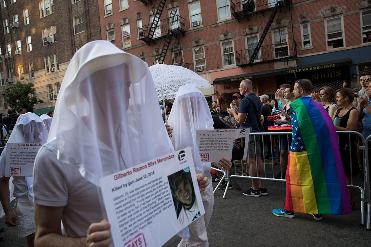 <p>People dressed in white hold photos of victims from the 2016 Pulse nightclub shooting during a memorial service and rally down the street from the historic Stonewall Inn, June 12, 2017 in New York City. (Photo: Drew Angerer/Getty Images) </p>