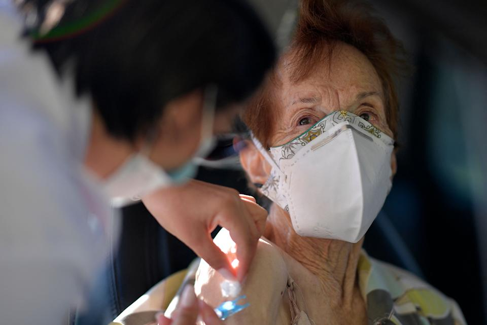 Military personnel of the Brazilian Army vaccinate elderly over 89 years of age, with the second dose of the AstraZeneca/Oxford vaccine against the novel coronavirus, COVID-19, at a drive-through vaccination centre in Belo Horizonte, State of Minas Gerais, Brazil, on May 1, 2021. (Photo by Douglas MAGNO / AFP) (Photo by DOUGLAS MAGNO/AFP via Getty Images)