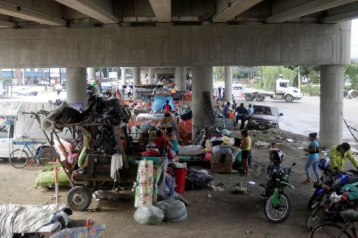 A general view shows people and their belongings under an overpass, where they are sheltered along other residents that lost their homes due to the floods caused by heavy rain brought by Hurricane Iota, in San Pedro Sula