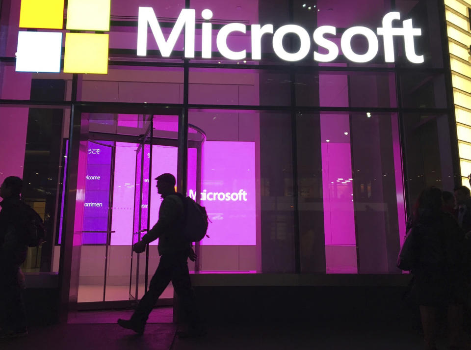 FILE - In this Nov. 10, 2016, file photo, people walk past a Microsoft office in New York. Three tech companies that have amassed unparalleled influence while reshaping the way we live released their latest quarterly report cards in a flurry late Tuesday, July 27, 2021. Although Apple, Microsoft and Google owner Alphabet Inc. make their money in different ways, the results for the April-June period served as another reminder of the clout they wield and why government regulators are growing increasingly concerned about whether they have become too powerful. (AP Photo/Swayne B. Hall, File)