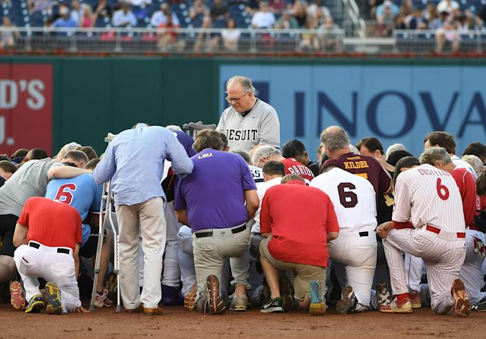 <p>JUN. 15, 2017 – Democrats and Republicans gather at second base for a prayer prior to the start of the Congressional baseball game with the house chaplain leading the way. Members of Congress took the field for their traditional Republicans vs. Democrats baseball game, with many wearing hats to honor Representative Steve Scalise, who was critically wounded by a gunman as his Republican team practiced a day before. (Photo: Jonathan Newton / The Washington Post via Getty Images) </p>