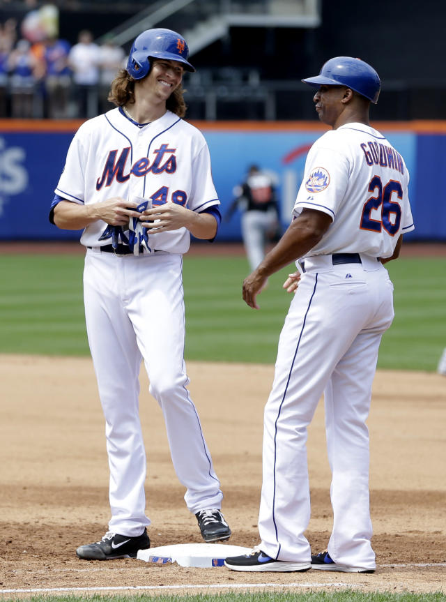 New York Mets' Jacob deGrom, left, smiles while talking to first base coach Tom Goodwin after hitting an RBI single during the fourth inning of the baseball game against the Miami Marlins at Citi Field, Sunday, July 13, 2014 in New York. (AP Photo/Seth Wenig)