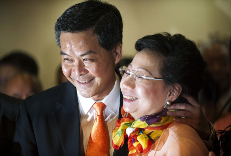 Former convener of Hong Kong's Executive Council Leung Chun-ying, left, and his wife Regina, right, celebrate his victory in the chief executive election Sunday, March 25, 2012. Leung was declared the semiautonomous territory's next chief executive by election officials after securing 689 votes from a 1,200-seat committee of business leaders and other elites. (AP Photo)