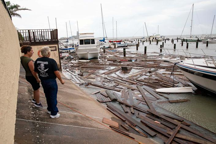 Boat owners survey the damage at Harbor Del Sol Marina as they check their boats the morning after Hurricane Hanna on July 26 in Corpus Christi, Texas.