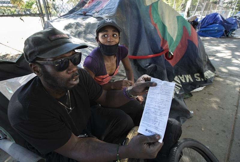 LOS ANGELES, CA-JUNE 3, 2020: Alex Jones, 31, and his girlfriend Maya Johnson, 18, are photographed outside their tent at a homeless encampment on 1st St. near Spring St. in downtown Los Angeles. They were both arrested and given tickets by the LAPD outside City Hall on Saturday night, where a protest was held over the death of George Floyd. Jones is holding the ticket that Johnson received. (Mel Melcon/Los Angeles Times)