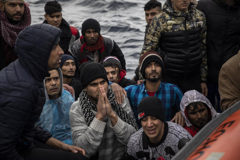 Men from Morocco and Bangladesh are assisted by members of Spanish NGO Open Arms on an overcrowded wooden boat in the Mediterranean Sea, international waters, off the Libyan coast, Friday, Jan. 10, 2020. (AP Photo/Santi Palacios)