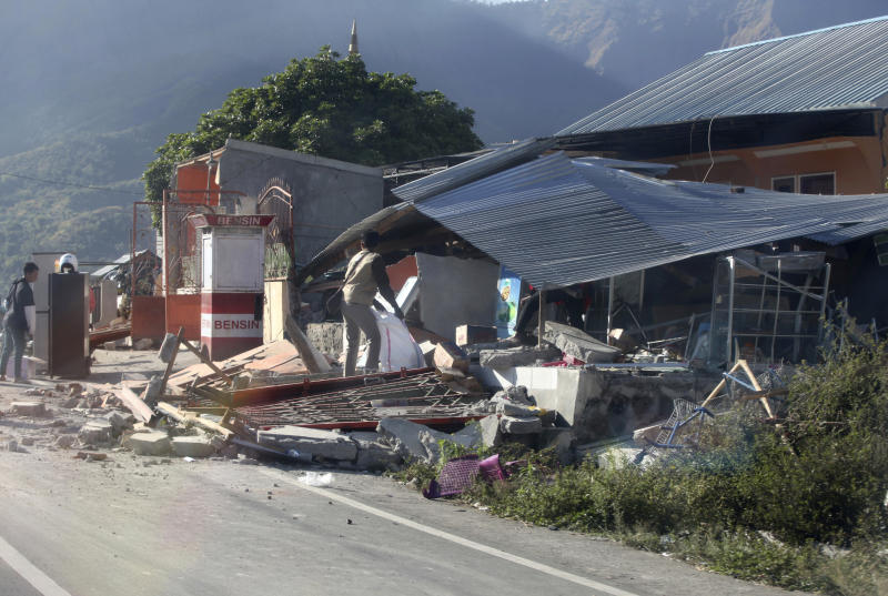 Indonesian men inspect buildings damaged by an earthquake in Sembalun, on Lombok Island, Indonesia, Monday, Aug. 6, 2018. The powerful earthquake struck the Indonesian tourist island of Lombok, killing a number of people and shaking neighboring Bali, as authorities on Monday said thousands of houses were damaged and the death toll could climb. (AP Photo/Adrial Pranandi)