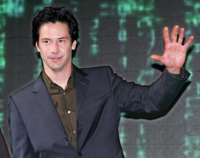"TOKYO, JAPAN: US movie star Keanu Reeves waves to journalists when he attends a press conference in Tokyo, 04 November 2003. Reeves is here to promote his new film ""Matrix Revolutions"" which will be shown tomorrow all over the world simultaneously. AFP PHOTO/Toru YAMANAKA (Photo credit should read TORU YAMANAKA/AFP via Getty Images)"