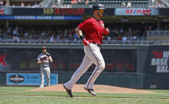 Minnesota Twins' Mitch Garver rounds the bases on a two-run home run off Baltimore Orioles pitcher Alex Cobb, background left, in the fifth inning of a baseball game Sunday, July 8, 2018, in Minneapolis. (AP Photo/Jim Mone)