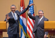 FILE - In this March 21, 2016 file photo, Cuban President Raul Castro, right, lifts up the arm of U.S. President Barack Obama at the conclusion of their joint news conference at the Palace of the Revolution in Havana, Cuba. While Raul has been the face of communist Cuba, its defiance of U.S. efforts to oust its socialist system and its efforts to forge a rapprochement with its longtime foe for the past decade, he formally announced on Friday, April 16, 2021 that he'd step down as head of the Communist Party, leaving Cuba without a Castro in an official position of command for the first time in more than six decades. (AP Photo/Ramon Espinosa, File)