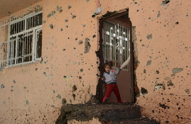 A girl stands at the entrance of a damaged house in the Sur district in Diyarbakir on December 11, 2015 (AFP Photo/Ilyas Akengin)