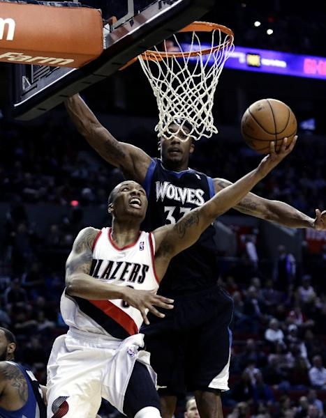 FILE- In this March 2, 2013, file photo, Portland Trail Blazers guard Damian Lillard, left, shoots against Minnesota Timberwolves forward Dante Cunningham during the second half of an NBA basketball game in Portland, Ore. The Trail Blazers are expected to announce Wednesday, May 1, 2013, Lillard as the league's Rookie of the Year. (AP Photo/Don Ryan, File)