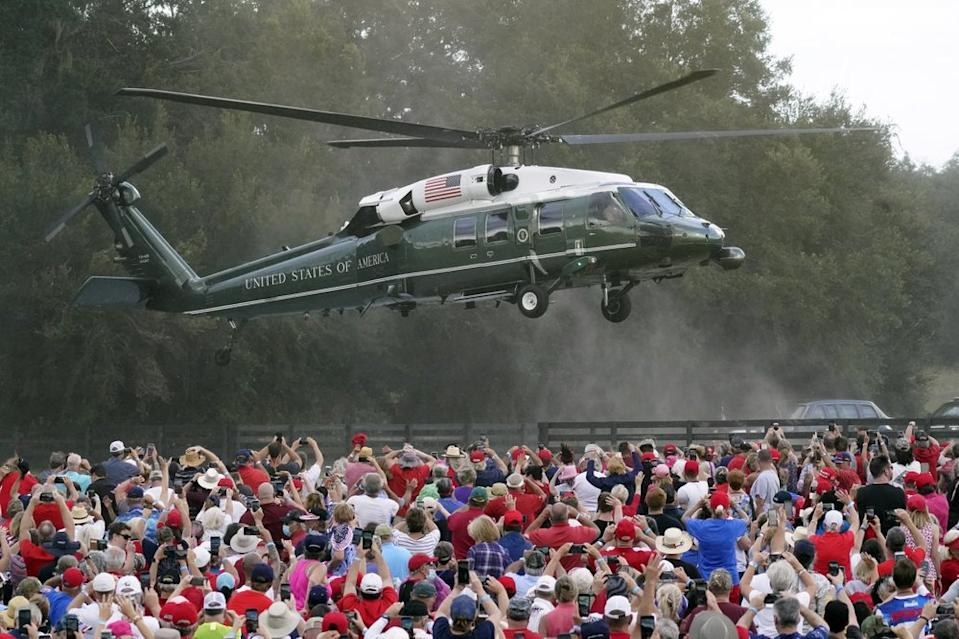 A crowd of supporters wave as Donald Trump lands via helicopter.