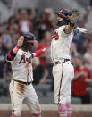 Atlanta Braves' Dansby Swanson, right, celebrates with Ozzie Albies after hitting a home run off Philadelphia Phillies' Aaron Nola during the first inning of a baseball game Sunday, May 9, 2021, in Atlanta. (AP Photo/Ben Margot)