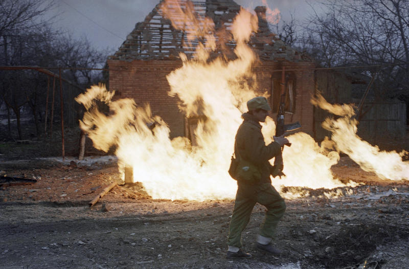 FILE - In this Saturday, Jan. 14, 1995 file photo a Chechen rebel fighter runs past a burning building in the center of Grozny, Chechnya, Russia. Two suspects in the Boston Marathon bombing have been identified to The Associated Press as coming from a Russian region near Chechnya. In the past, insurgents from Chechnya and neighboring restive provinces in the Caucasus have been involved in terror attacks in Moscow and other places in Russia. (AP Photo/Efrem Lukatsky, File)