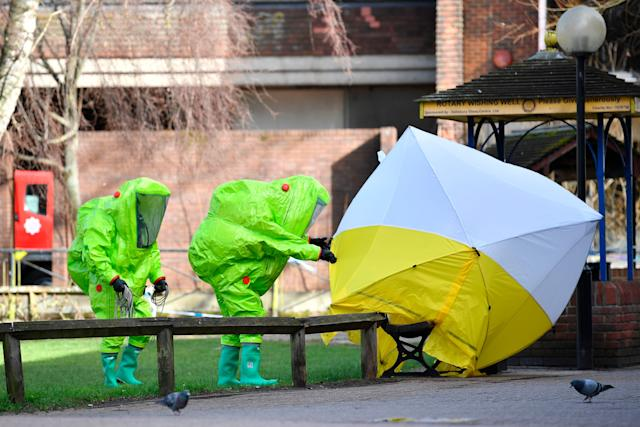 Members of emergency services in green biohazard encapsulated suits fix a tent over the bench where Sergei Skripal and his daughter were found on March 4 in critical condition in Salisbury, England.