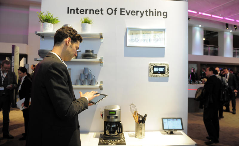 """In this Tuesday, Feb. 26, 2013, photo, a man checks his device in front of a banner """"Internet of Everything"""" at the Mobile World Congress, the world's largest mobile phone trade show, in Barcelona, Spain. The first wave of the wireless revolution was getting people to talk to each other through cellphones. The second, it seems, will be getting things to talk to each other, with no human intervention: cars that talk to your insurance company's computers, bathroom scales that talk to your phone, and electric meters that talk to your air conditioners. So-called machine-to-machine technology all the buzz at this year's largest wireless trade show, and some analysts believe these types of connections will outgrow the traditional phone business in less than a decade. (AP Photo/Manu Fernandez)"""