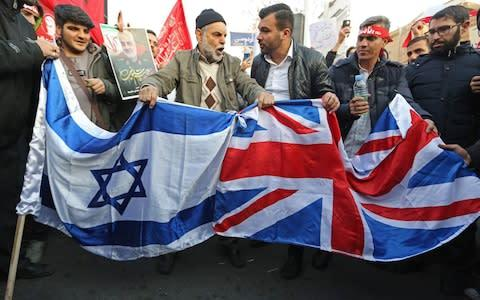 <span>Iranian demonstrators prepare to burn a Union flag and Israeli flag in front of the British embassy in Iran's capital Tehran on January 12</span>