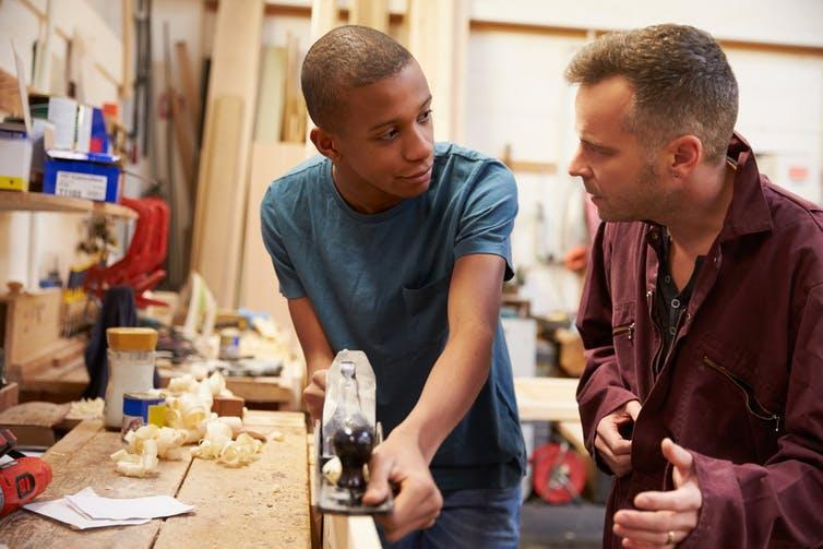 Mentor talks to young male apprentice planing some wood