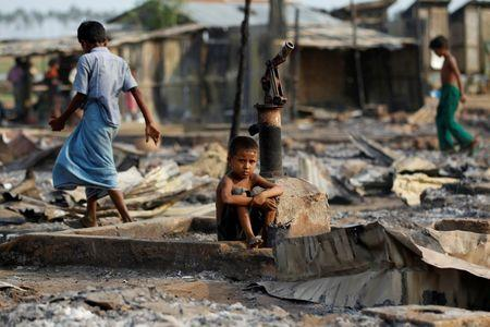 A boy sit in a burnt area after fire destroyed shelters at a camp for internally displaced Rohingya Muslims in the western Rakhine State near Sittwe, Myanmar May 3, 2016. REUTERS/Soe Zeya Tun
