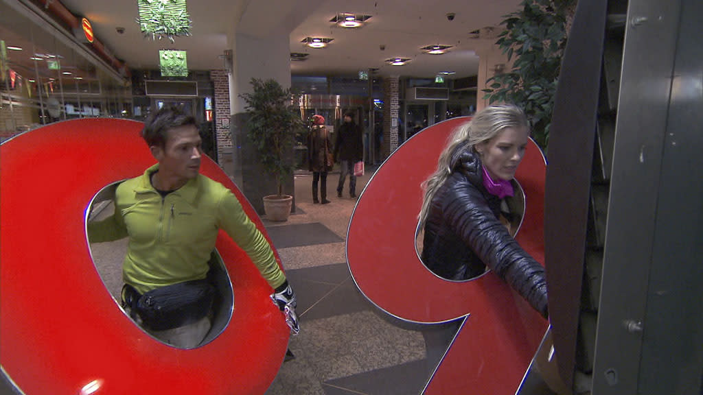 """The Ultimate Fun House"" - In Detour B, Newlyweds Max (left) and Katie (right) must deliver illuminated billboard letters on foot in order to receive the next clue, on ""The Amazing Race."""