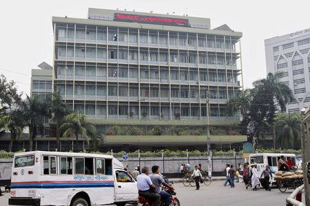 FILE PHOTO: Commuters pass by the front of the Bangladesh central bank building in Dhaka
