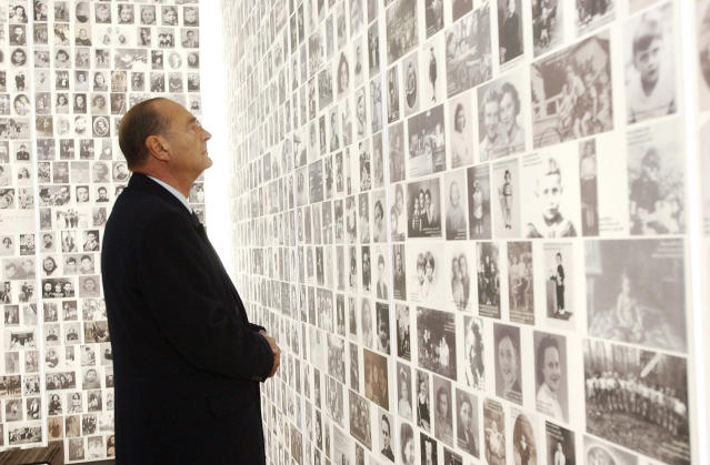 FILE - In this Jan.27, 1995 file photo, French President Jacques Chirac looks at pictures of Jews sent to Nazi death camps from France as he inaugurates Paris' new memorial to the Holocaust. Jacques Chirac's legacy was especially alive at the Shoah Memorial in Paris, where an exhibition features a photo of him pronouncing one of his most decisive speeches. Speaking in 1995 on the anniversary of the July 16, 1942, roundup of 13,000 Jews, Chirac acknowledged for the first time France's role in the Holocaust.(AP Photo/Jacques Brinon/Pool, File)