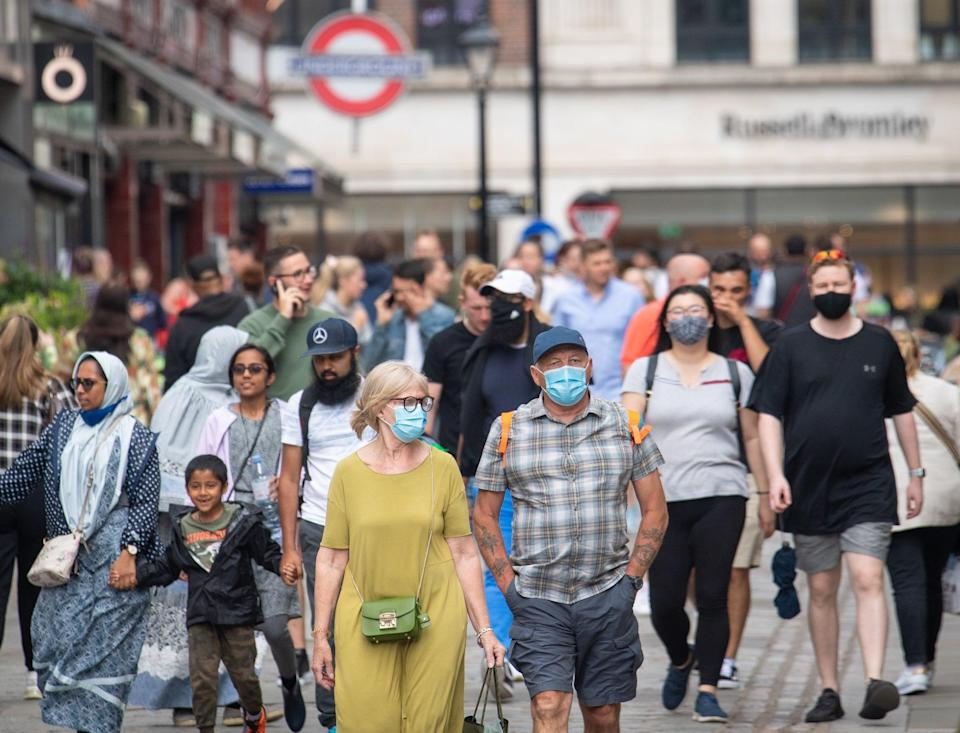 People wearing face masks among crowds of pedestrians in Covent Garden, London.(PA) (PA Wire)