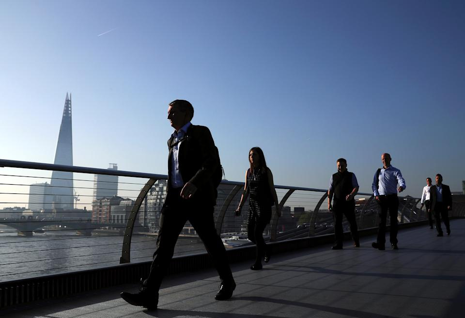 People cross the Millenium Bridge in front of the Shard on a sunny morning in London, Britain, May 8, 2018. REUTERS/Hannah McKay