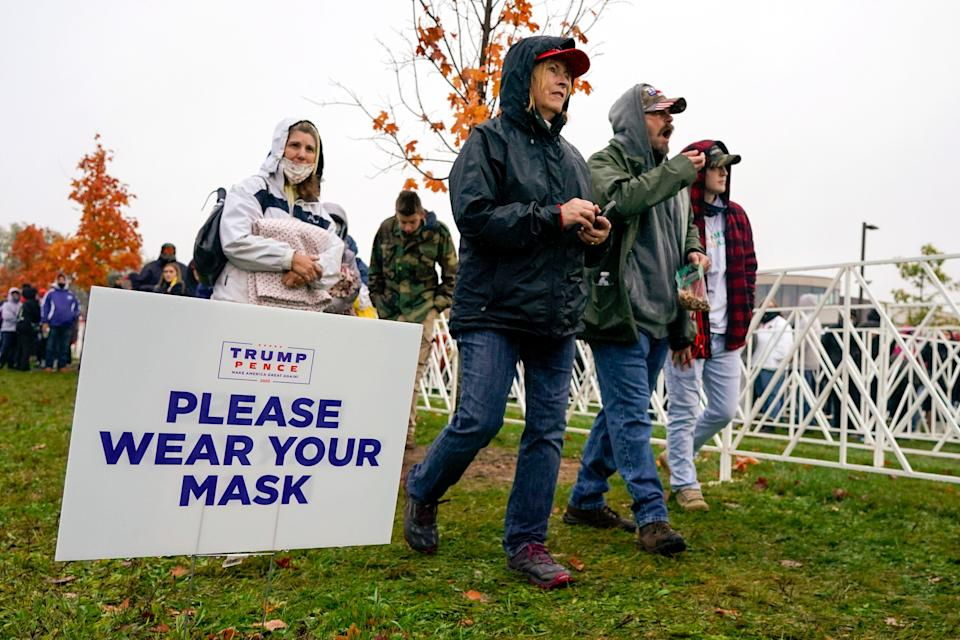 Supporters walk by a sign reminding them to wear a face mask as they arrive to hear President Donald Trump speak Monday at a campaign rally in Allentown, Pennsylvania. (Photo: Chris Szagola/ASSOCIATED PRESS)