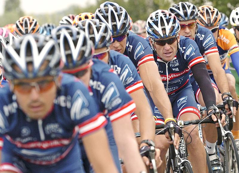 "FILE - This July 5, 2004 file photo shows U.S. Postal Service team leader and five-time Tour de France winner Lance Armstrong, third from right, framed by his teammates as the pack rides during the second stage of the 91st Tour de France cycling race between Charleroi and Namur, Belgium. The U.S. Anti-Doping Agency says 11 of Lance Armstrong's former teammates testified against him in its investigation of the cyclist, revealing ""the most sophisticated, professionalized and successful doping program that sport has ever seen.""  USADA will deliver its reasoned decision against Armstrong later Wednesday, Oct. 10, 2012,  a summary of the facts it used to hand him a lifetime suspension and erase his seven Tour de France titles. (AP Photo/Christophe Ena, File)"