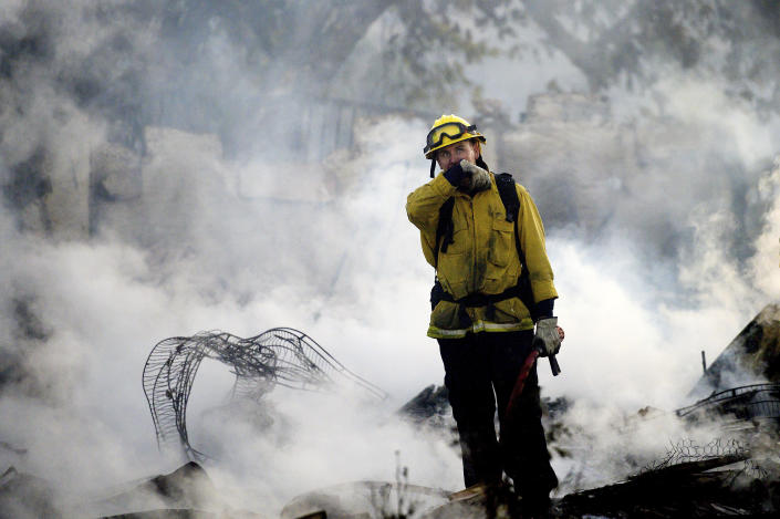 A firefighter pauses while mopping up at a leveled home as the Hillside Fire burns in San Bernardino, Calif., on Thursday, Oct. 31, 2019. The blaze, which ignited during red flag fire danger warnings, destroyed multiple residences. (AP Photo/Noah Berger)