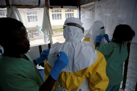 FILE PHOTO: Health workers dress in Ebola protective suits before starting their shift at an Ebola transit centre in the town of Katwa near Butembo