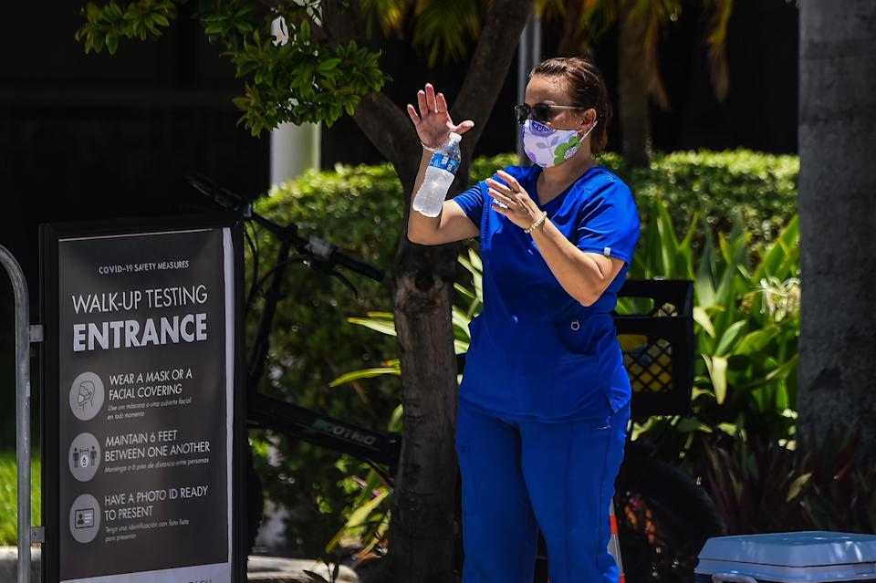 "A woman waits for her testing at a ""walk-in"" and ""drive-through"" coronavirus testing site in Miami Beach, Florida on June 24, 2020. - With coronavirus cases surging across the US South and West, officials are once again imposing tough measures, from stay-at-home advice in worst-hit states to quarantines to protect recovering areas like New York. Nearly four months after the United States reported its first death from COVID-19, the nation faces a deepening health crisis as a wave of infections hits young Americans and experts issue new acute warnings. (Photo by CHANDAN KHANNA / AFP) (Photo by CHANDAN KHANNA/AFP via Getty Images)"