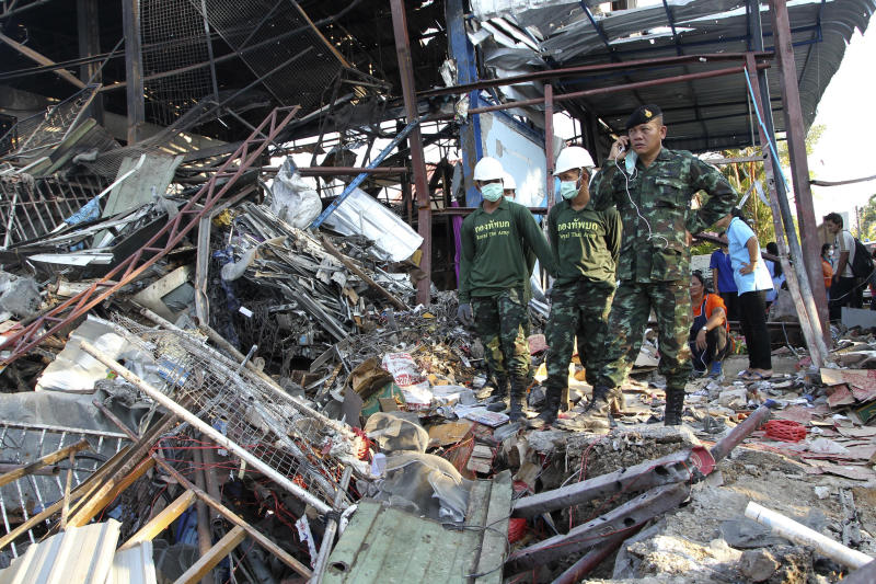 Thai soldiers stand next to a crater created by a bomb explosion at a scrap shop in Bangkok, Thailand, Wednesday, April 2, 2014. Workers at the shop accidentally detonated a large bomb believed to have been dropped during World War II, killing at least seven people and injuring 19 others, police said. (AP Photo/Apichart Weerawong)