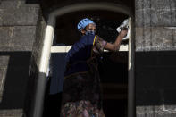 "A woman cleans the window of a house in the capital Addis Ababa, Ethiopia Friday, Nov. 13, 2020. Tensions over the deadly conflict in Ethiopia are spreading well beyond its cut-off northern Tigray region, as the federal government said some 150 suspected ""operatives"" accused of seeking to ""strike fear and terror"" throughout the country had been detained. (AP Photo/Mulugeta Ayene)"