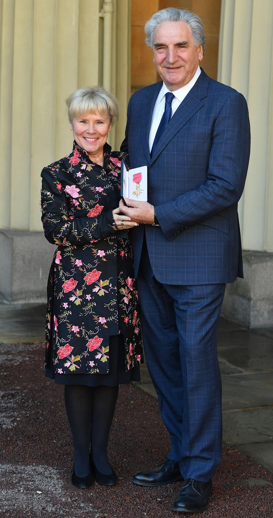 British actor Jim Carter (R) poses with his wife Imelda Staunton (L) after being appointed Officer of the Order of the British Empire (OBE) at an investiture ceremony at Buckingham Palace in London on March 14, 2019, for his services to drama. (Photo by John Stillwell / POOL / AFP) (Photo credit should read JOHN STILLWELL/AFP/Getty Images)