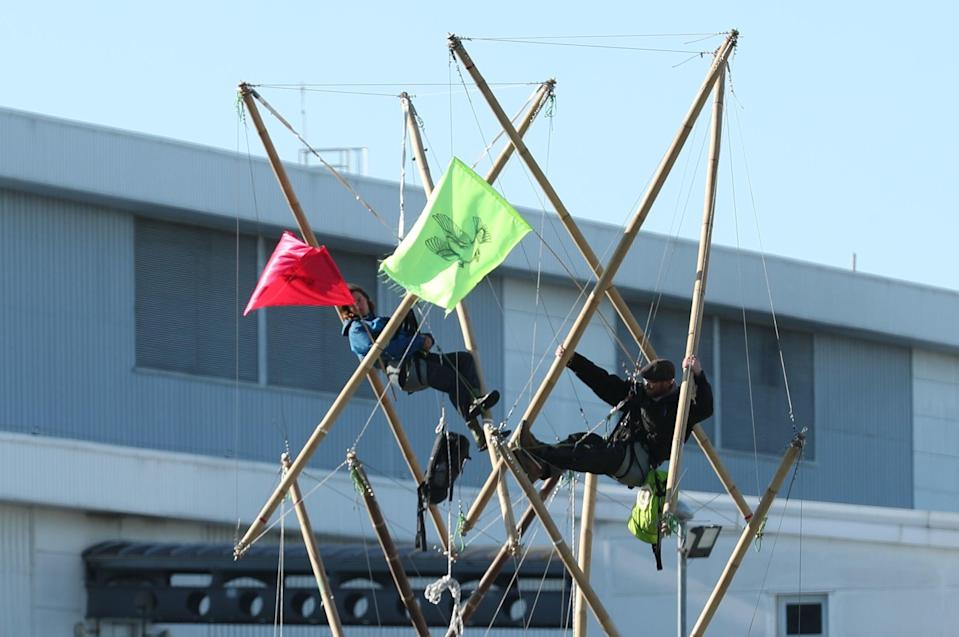 Protesters lock themselves on to bamboo structures outside the Newsprinters plant in Waltham Cross (PA)