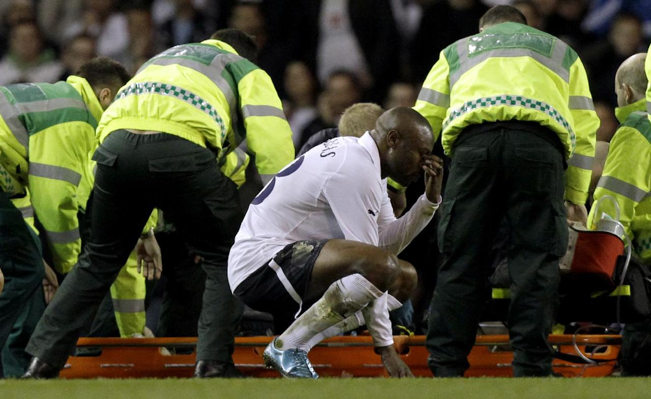 Bolton Wanderers' Fabrice Muamba is obscured by medical staff trying to resuscitate him after collapsing as Tottenham Hotspur player William Gallas reacts during the English FA Cup quarterfinal soccer match between Tottenham Hotspur and Bolton Wanderers at White Hart Lane stadium in London, Saturday, March 17, 2012. Bolton midfielder Fabrice Muamba has been carried off the field at Tottenham after medics appeared to be trying to resuscitate him during an FA Cup quarterfinal that was abandoned. Muamba went to the ground in the 41st minute with no players around him and the game was immediately stopped. (AP Photo/Matt Dunham)