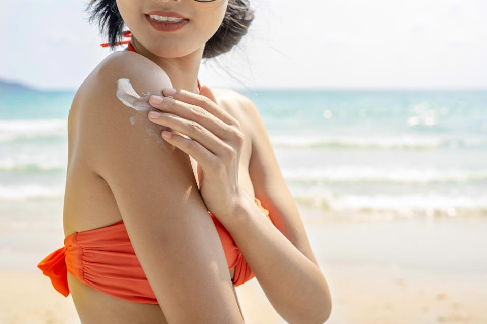 A woman in a bikini puts sunscreen on her shoulder.
