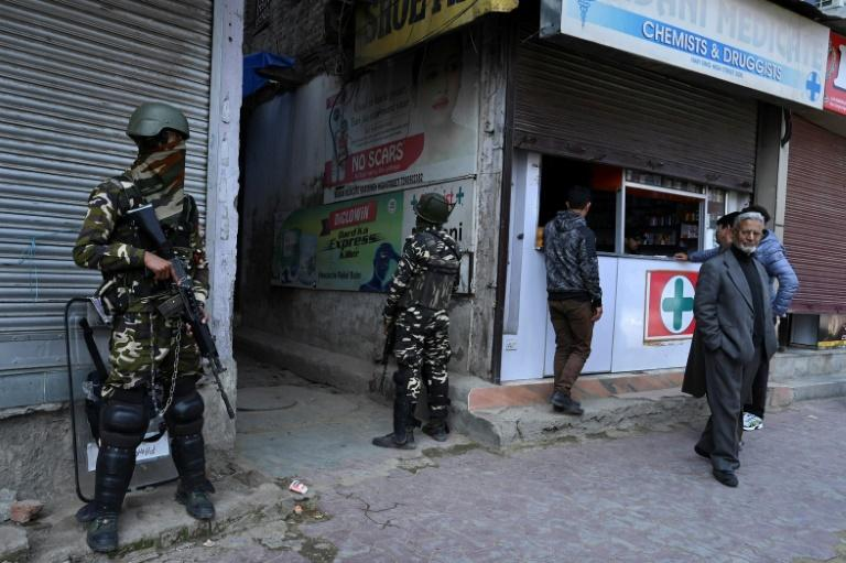 Indian paramilitary troopers stand guard outside a chemist shop during a lockdown in Srinagar, Kashmir (AFP Photo/TAUSEEF MUSTAFA)