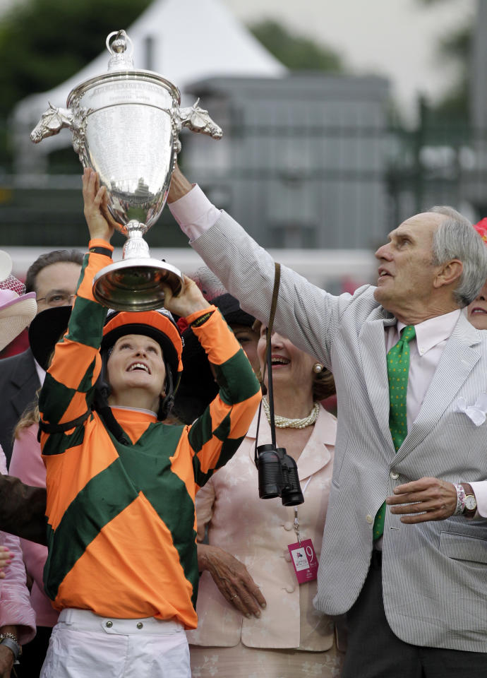 Rosie Napravnik, left, and owner Brerton Jones hold up the winning trophy after Believe You Can won the 138th running of the Kentucky Oaks horse race at Churchill Downs Friday, May 4, 2012, in Louisville, Ky. (AP Photo/Mark Humphrey)