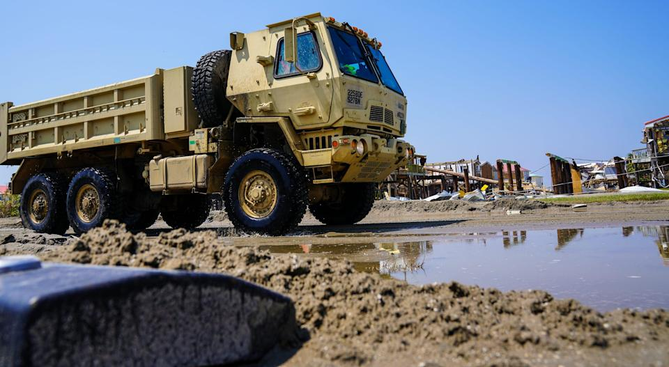 A National Guard dump truck clears sand from the inundated streets of Grand Isle, Louisiana following the passage of Hurricane Ida.