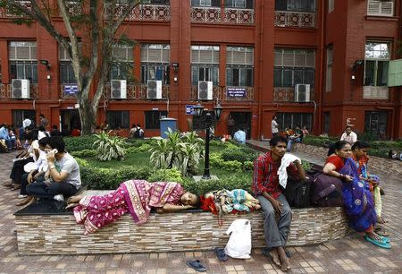 Relatives of patients rest in the premises of a government-run hospital in Kolkata