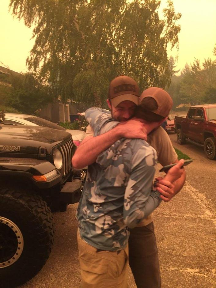 Nick and Chris Myron hug after finding out that their father is safe and alive after escaping the Beachie Creek Fire.