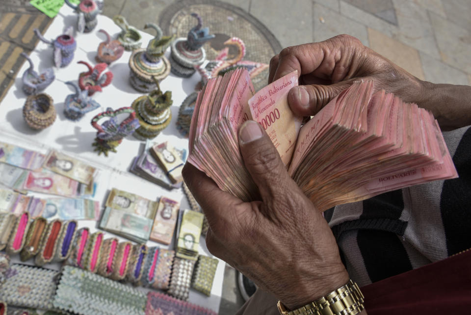 BOGOTA, COLOMBIA - MAY 18: Colombian designer Luis Orlando Ortega counts Venezuelan devalued and out of circulation banknotes Bolivares Fuertes at the main avenue of historic downtown Bogota, Colombia, on May 18, 2019. Mr. Ortega, 60 year-old, lived 43 years in Venezuela, returned to Colombia 2 years ago, escaping the economic and social crisis in Venezuela and now earns his living selling handicrafts made with the devalued Venezuelan Bolivares in the Colombian capital. Colombian and Venezuelan artists fold Venezuelan devalued banknotes into swans, baskets, model cars and purses or paint them with famous characters to offer them in the touristic area of La Candelaria. They use currencies out of circulation and also current legal banknotes of 2 and 5 Bolivares Soberanos (Sovereign Bolivar). On August 20, 2018, Venezuela changed its currency from Bolivar Fuerte (Strong Bolivar) to Sovereign Bolivar at a rate of 100,000 to 1. Due to hyperinflation, some Venezuelan banknotes are no longer found in circulation as their value decreased but remain legal tender. Cash is worth so little that banknotes are often burnt or thrown away. According to the World Economic Outlook report released by International Monetary Found on April 2019, Venezuela is expected to suffer this year a 10 million percent inflation raise, making it the most miserable economy in the world. As a consequence, some banknotes turned almost obsolete. (Photo by Guillermo Legaria/Getty Images)