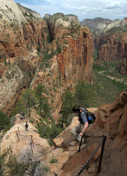FILE - In this May 8, 2011, file photo, hikers climb down the Angels Landing trail in Zion National Park, in Utah. Zion National Park announced Monday, March 23, 2020, it is closing its campgrounds and part of a popular trail called Angel's Landing that is often crowded with people due to coronavirus. The top part of the hike that is being closed is bordered by steep drops and ascends some 1,500 feet (457 meters) above the southern Utah park's red-rock cliffs, offering sweeping views. (Jud Burkett/The Spectrum via AP, File)