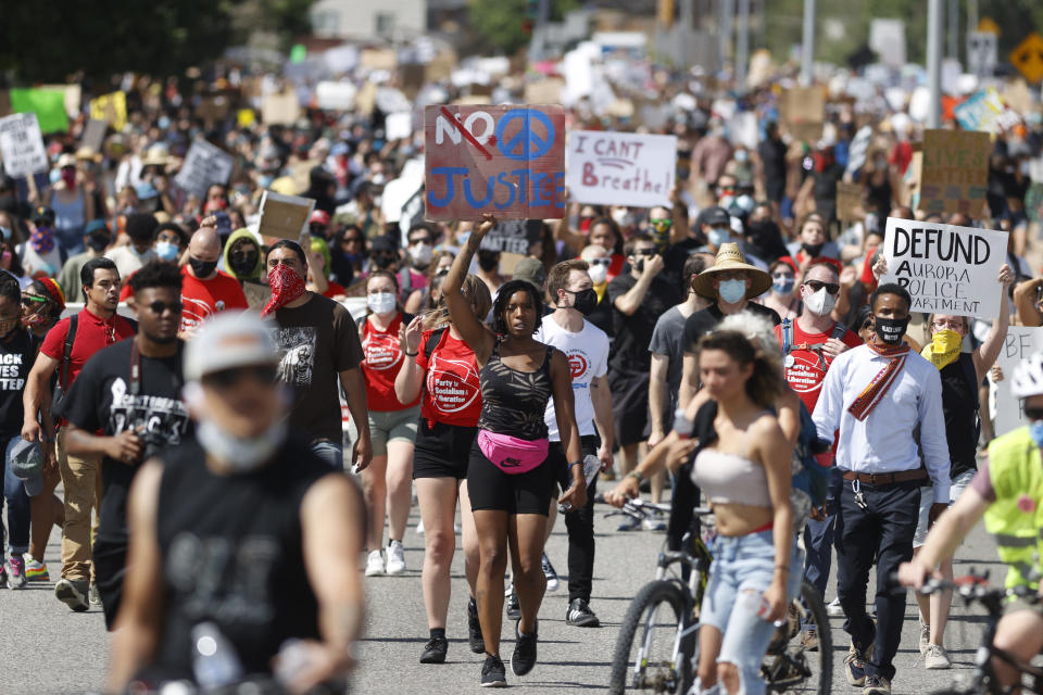 FILE - In this Saturday, June 27, 2020, file photo, demonstrators march down Sable Boulevard during a rally and march over the death of 23-year-old Elijah McClain, in Aurora, Colo. State legislatures across the U.S. are pushing an array of policing reforms after the demonstrations sparked by the death of George Floyd last spring, from banning chokeholds to making it easier to hold officers legally accountable for their actions. (AP Photo/David Zalubowski, File)