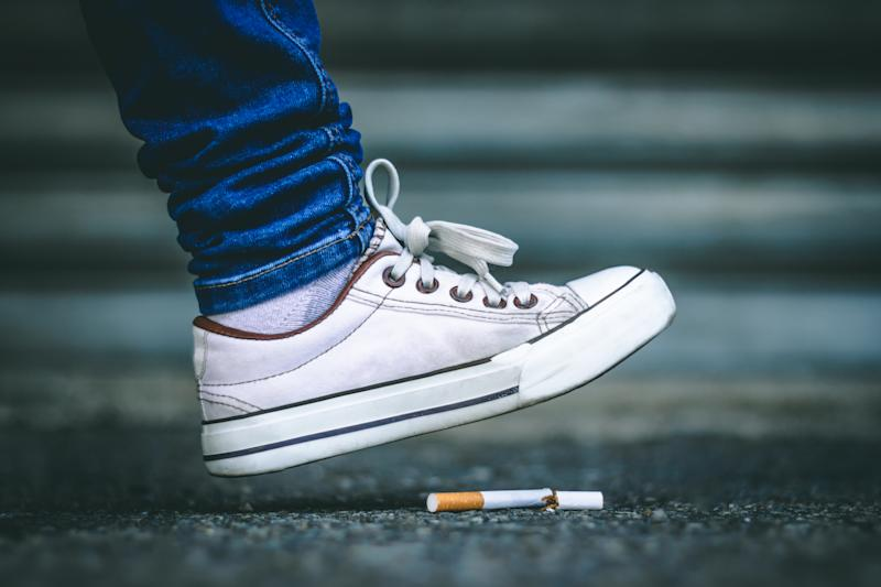 Young person's foot wearing white sneakers and jeans stepping on a broken cigarette sitting on the rough asphalt – Concept image for no smoking day and quitting toxic and dangerous habits